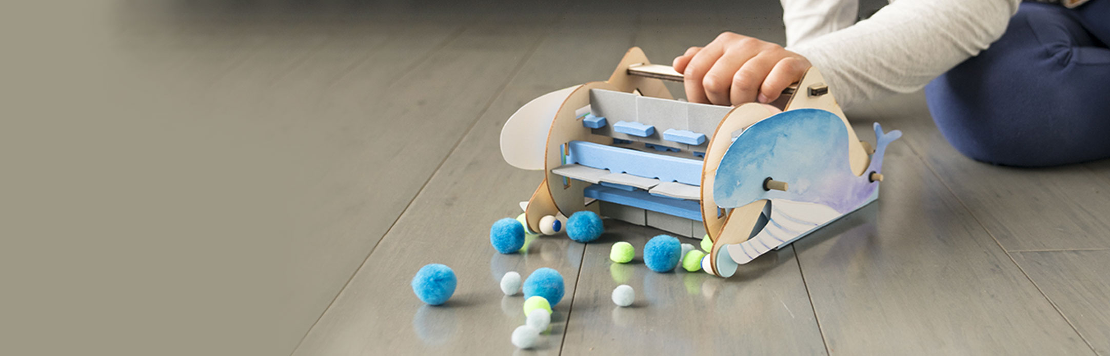 Child playing with Kiwi Crate's Mechanical Sweeper